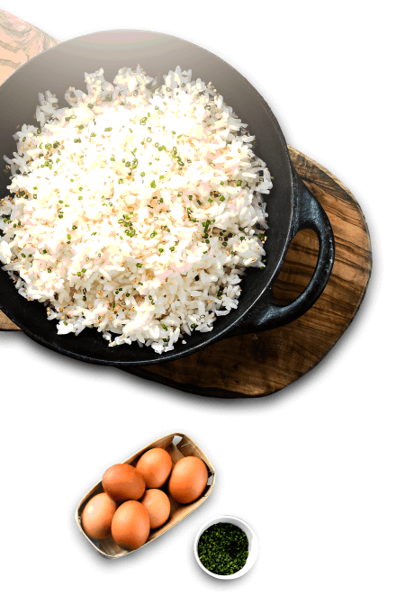 Imagem de cima de uma panela de arroz e ao lado um recipiente com ovos