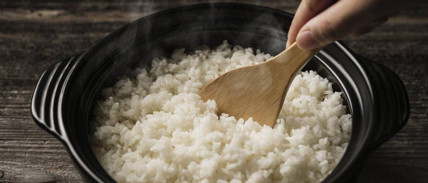 Imagem de uma panela cheia de arroz soltinho com uma colher