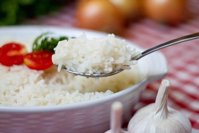 Imagem de prato de arroz soltinho e uma colher tirando uma porção.